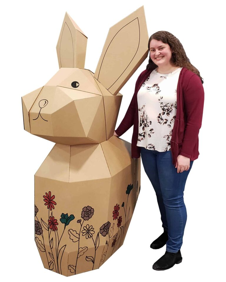 American Box employee standing next to a corrugated bunny, larger than her with illustrated flowers around the base