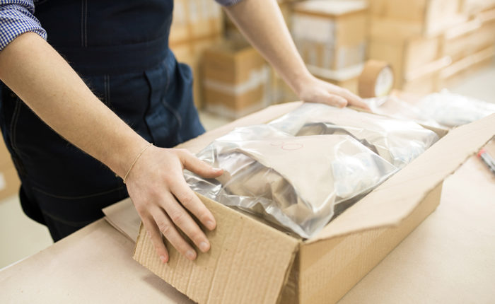 worker packing items in corrugated box while working at fulfillment facility