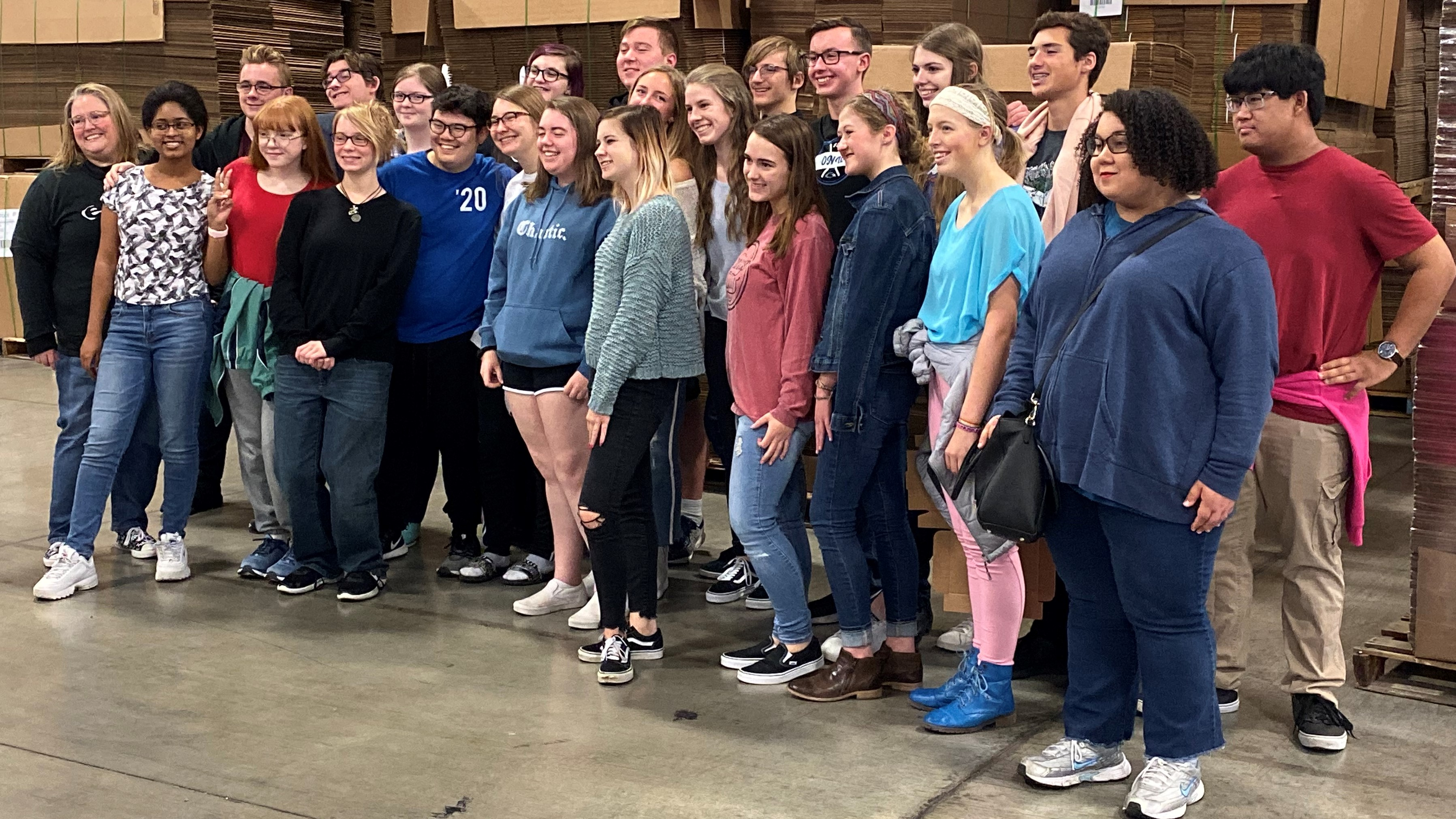 Olathe North-West High School Graphic Design students standing in front of stacks of corrugated