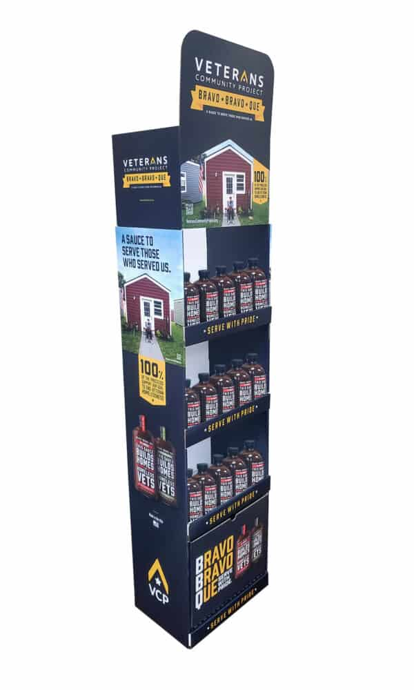 A tall floorstand BBQ display with text 'Veterans Community Project Bravo Bravo Que'
