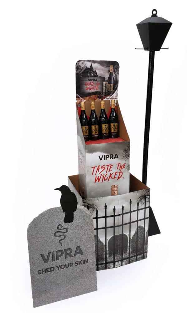 Wine bottle display with corrugated lamp, gravestone, and printed fence wrap
